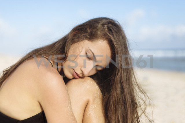 Attractive young woman with closed eyes on the beach - KNTF00989