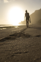 Indonesia, Bali, woman walking on the beach at sunset - KNTF00995
