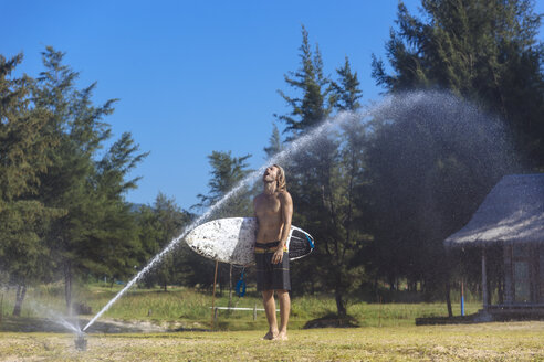 Young man with surfboard refreshing at sprinkler - KNTF00998