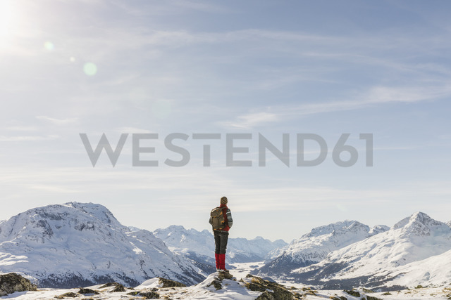 Switzerland, Engadin, hiker in mountainscape looking at view - MRAF00259