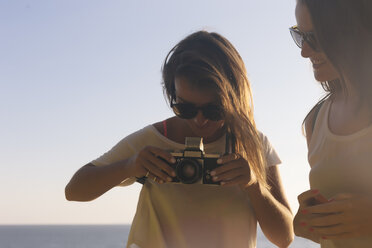 Indonesia, Bali, Lembongan island, two young women with camera at the ocean - KNTF01002