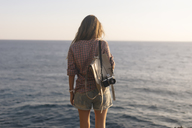 Indonesia, Bali, Lembongan island, young woman with camera at ocean coastline - KNTF01005