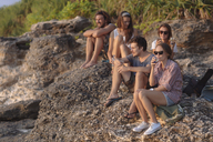 Indonesia, Bali, Lembongan island, friends having a drink at ocean coast - KNTF01008