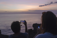 Indonesia, Bali, Lembongan island, friends at ocean coast at dusk taking cell phone pictures - KNTF01011