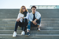 Portrait of stylish young couple sitting on stairs outdoors - AFVF00255