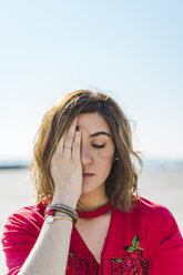 Portrait of young woman outdoors covering one eye - AFVF00261