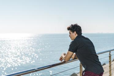 Young man at the coast looking at view - AFVF00270