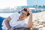 Portrait of happy young man lying in sand on the beach - AFVF00273