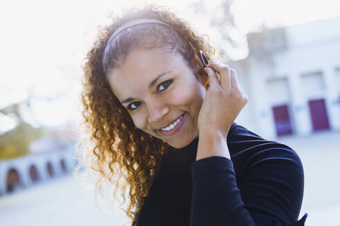 Portrait of smiling young woman outdoors putting on earphone - JSRF00001