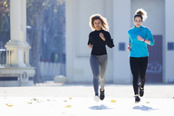Two focused young women running listening to music - JSRF00004