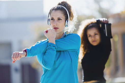 Two focused sportive young women stretching listening to music - JSRF00007
