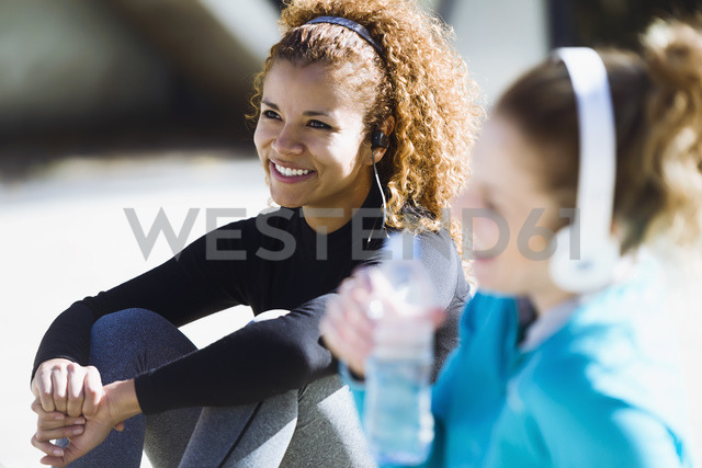 Two smiling sportive young women having a break listening to music - JSRF00016