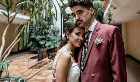 Portrait of groom embracing beautiful bride - DAPF00887