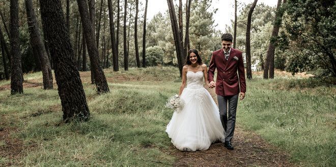 Happy bride and groom walking in forest - DAPF00896