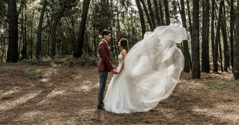 Bride with windswept wedding dress and groom standing in forest holding hands - DAPF00899