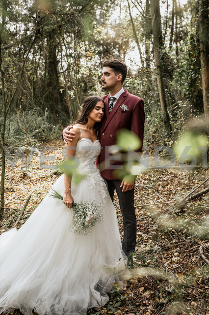 Groom embracing bride with closed eyes in forest - DAPF00902