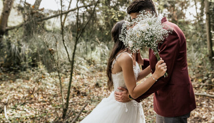 Unrecognizable bride and groom kissing in forest behind bouquet of flowers - DAPF00905
