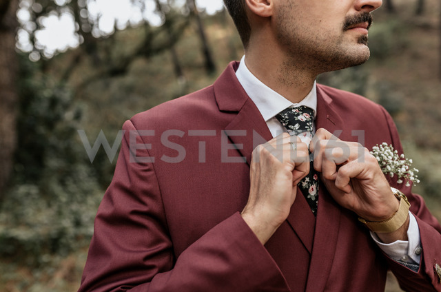 Close-up of man wearing a suit in forest adjusting his tie - DAPF00908
