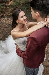Portrait of beautiful bride embracing and looking to man outdoors - DAPF00914