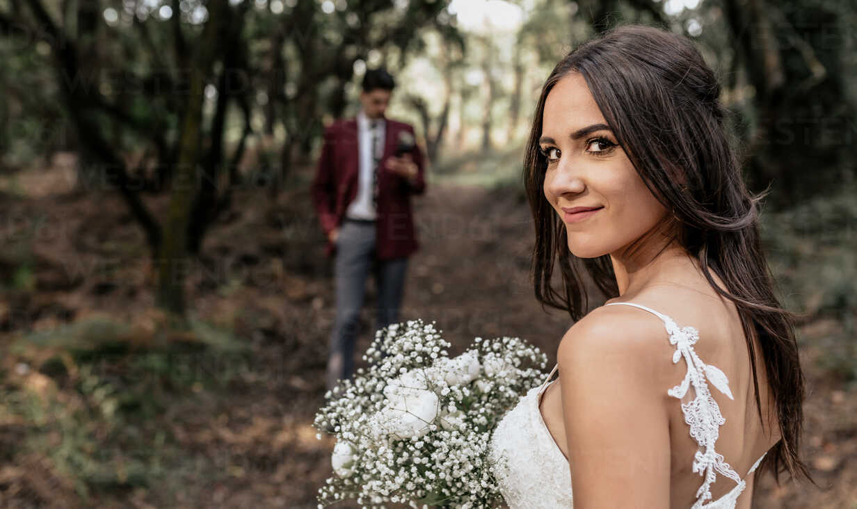 Portrait of smiling bride holding bouquet of flowers in forest with groom in background - DAPF00917 - David Pereiras/Westend61