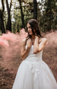 Woman with closed eyes wearing wedding dress in forest surrounded by clouds of smoke - DAPF00920