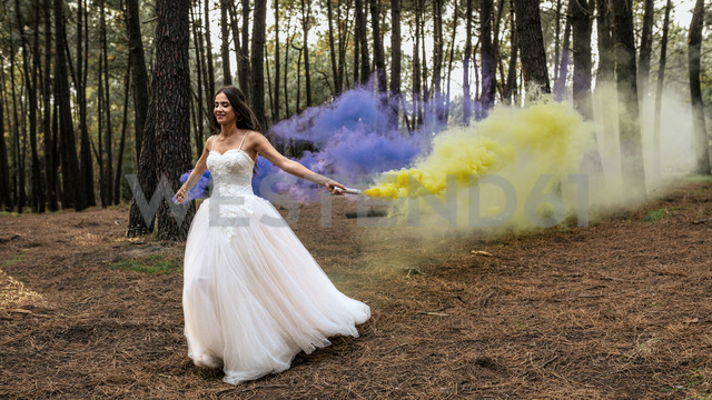 Woman wearing wedding dress in forest holding smoke torches - DAPF00923
