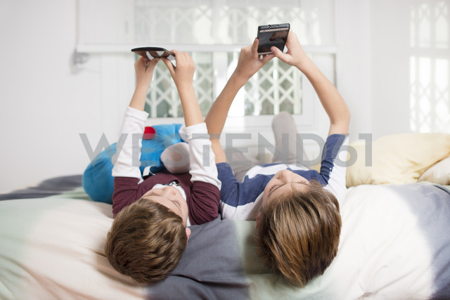 Two boys lying on bed at home using cell phones - SKCF00332