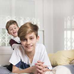 Portrait of smiling boy with younger brother lying on bed at home - SKCF00335