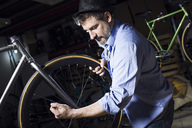 Man working on bicycle in workshop - JSRF00021