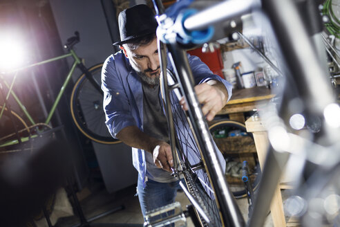 Man working on bicycle in workshop - JSRF00027