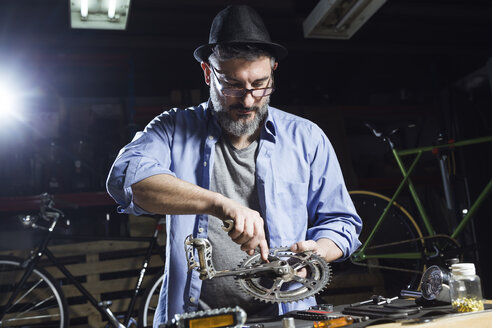 Man working on bicycle in workshop - JSRF00030
