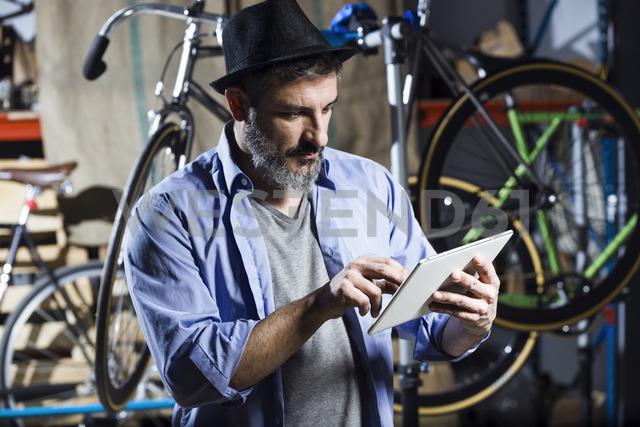 Man in bicycle workshop using tablet - JSRF00033
