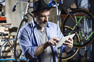 Man in bicycle workshop using tablet - JSRF00033