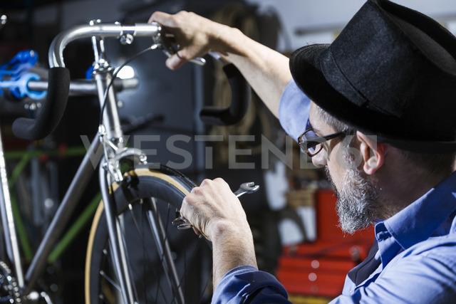 Man working on bicycle in workshop - JSRF00036