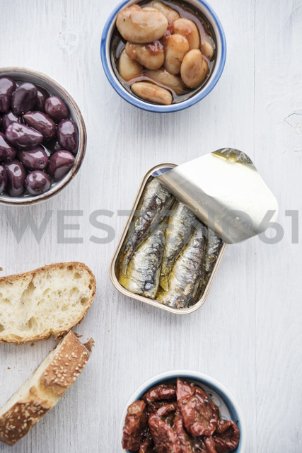 Tin can of sardines in oil, bowls of pickled vegetables and slices of bread - IPF00439