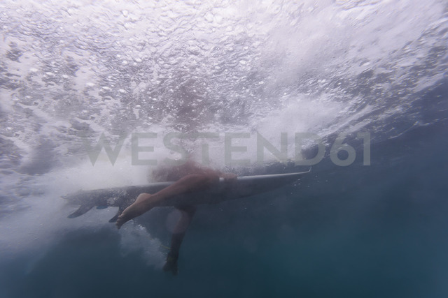 Indonesia, Bali, surfer sitting on surfboard - KNTF01014