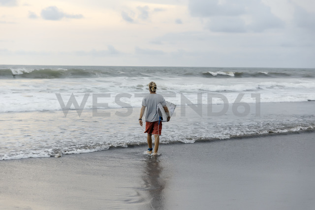 Indonesia, Bali, surfer walking into water - KNTF01017