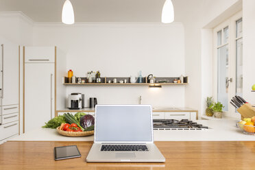Laptop and tablet on kitchen counter - JHAF00012