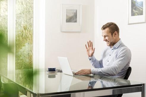 Young man smiling and waving at his laptop - JHAF00015