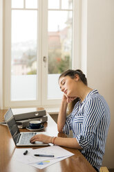 Young woman asleep in front of her laptop at home - JHAF00018