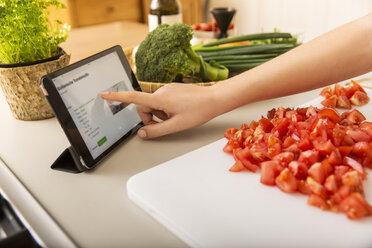 Young woman cutting tomatoes on kitchen counter and reading recipe on tablet - JHAF00027