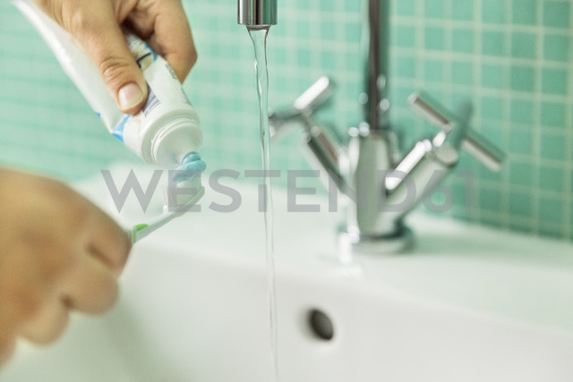 Hands putting toothpaste on toothbrush in bathroom - JHAF00030