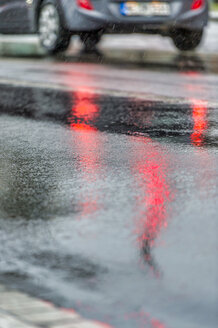 Germany, mirrored red light of traffic light on rain-wet road, rear lights of car - FRF00635