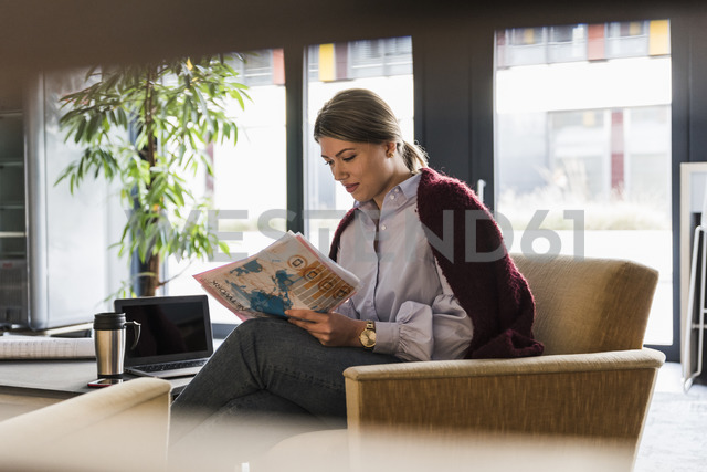 Young woman sitting in armchair reading documents - UUF12821