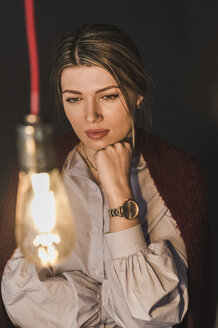 Young woman looking at illuminated light bulb - UUF12830