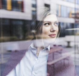 Smiling young woman looking out of window - UUF12839