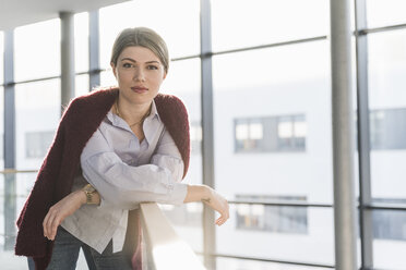 Portrait of confident young woman leaning on railing in bright office building - UUF12848
