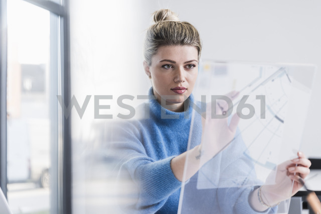 Young woman working on transparent design in office - UUF12851