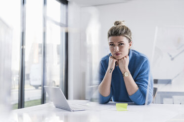 Portrait of young woman with laptop at desk in office - UUF12854