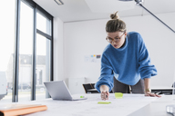 Young woman with laptop working on plan at desk in office - UUF12857